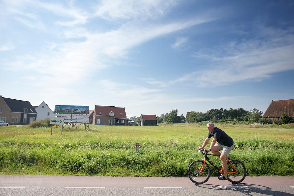 Een man rijdt op een fiets door de weilanden bij Ouddijk.<br /> <br /> A man riding a bicycle through the meadows at Ouddijk.