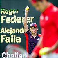 Engeland, Londen, 28-07-2012.<br /> Olympische Spelen.<br /> Tennis, Heren, Enkel.<br /> Federer - Falla.<br /> Alles is veel kleurrijker op Wimbledon, zoals Federer die het rode shirt van Zwitserland draagt en de ballenjongen die de kleurrijke kleding  van de vrijwillegers van de Spelenaan heeft.<br /> Foto : Klaas Jan van der Weij