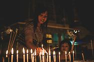 Yangon, Myanmar - November 15, 2011: A Burmese mother and daughter light candles at the Shwedagon Pagoda in Yangon.
