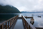 A boat pier extends out on a misty morning onto Lake Crescent at the Olympic Park Institute in Olympic National Park, Washington.