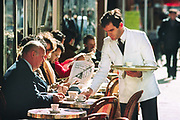 A waiter in a white jacket serves coffee to a large man at a table on the pavement outside a cafe with typical tables and chairs, 10th May 1980, Paris, France.