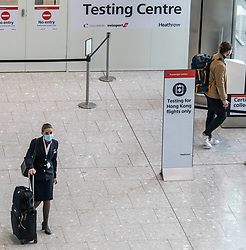 © Licensed to London News Pictures. 20/10/2020. London, UK. A flight attendant and passenger walk past a testing centre at Heathrow Terminal 5. A one hour Covid-19 testing centre at London Heathrow for Hong Kong and Italy passengers has opened up at London Heathrow. Two facilities one at Terminal 5 and the other at Terminal 2 will offer much quicker results than the NHS as samples don't need to be sent away to be tested. Prime Minister Boris Johnson is expected to announce a Tier 3 lockdown for Manchester tonight as coronavirus levels of infections continue to escalate throughout the UK. Photo credit: Alex Lentati/LNP