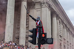 Licensed to London News Pictures. 11/07/2021. London, UK. An England fan dressed as a knight, climbs a traffic light as fans go wild as they gather at St Martin-in-the-Fields Church at Trafalgar Square in London ahead of England's Euro 2020 finals match. England take on Italy in the Euro 2020 final at the iconic Wembley Stadium this evening. Photo credit: Alex Lentati/LN