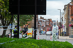© Licensed to London News Pictures. 07/09/2020. High Wycombe, UK. A forensic investigator stands in a grassy area on a traffic island after reports of a stabbing on Easton Street in High Wycombe, a large cordon centred around the High Wycombe Magistrates Court. Photo credit: Peter Manning/LNP