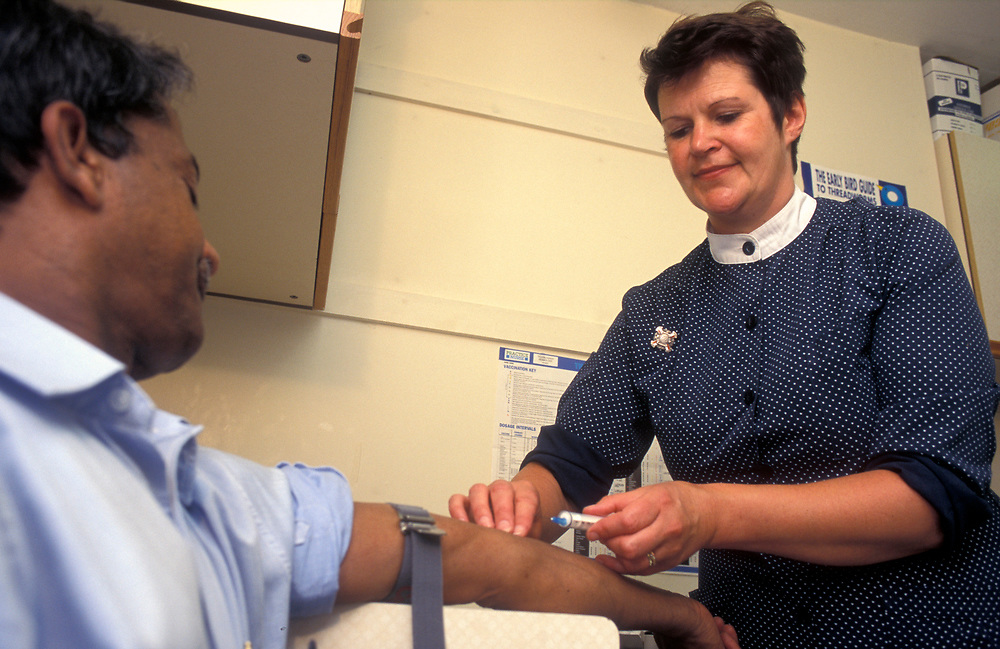 Practice nurse taking blood at a doctors surgery,