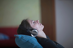 Young woman relaxing and listening to music at home, Freiburg im Breisgau, Baden-Wuerttemberg, Germany