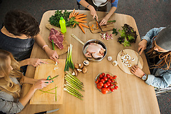 Friends cutting vegetables in the kitchen, Munich, Bavaria, Germany