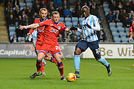 Oldham Athletic defender Brian Wilson holds up Coventry City striker Marc-Antoine Fortune during the Sky Bet League 1 match between Coventry City and Oldham Athletic at the Ricoh Arena, Coventry, England on 19 December 2015. Photo by Alan Franklin.