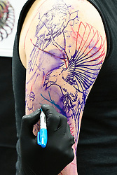 © under license to London News Pictures. 29/01/2011. A tattoo artist creates an original design at the fourth Brighton Tattoo Convention held at Brighton Racecourse on the 29th and 30th of January. Picture credit should read: Julie Edwards/London News Pictures
