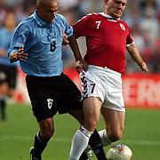 Uruguay's Gustavo Varela battles with Denmark's Thomas Gravesen