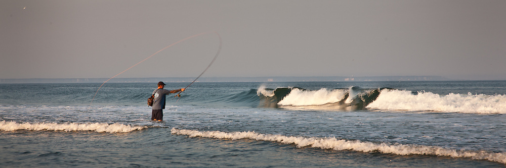 The water of the Atlantic Ocean was warm by Maine standards when this fisherman waded in for a bit of surf fishing.   Aspect Ratio 1w x 0.333h.