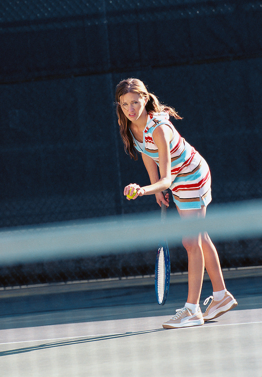 A young woman ready to serve a tennis ball<br />