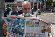 Smoking a cigarette with a face mask while reading a newspaper The outbreak of COVID-19 has forced governments around the world to impose a civil quarantine. The outcome of this are empty streets and public places. The only stores that remain open are food shops and essential products. Photographed at the Netanya market, Israel on March 29th 2020