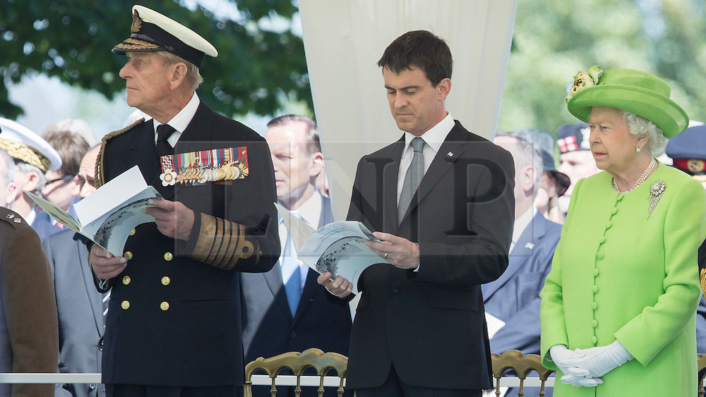 © Licensed to London News Pictures. 06/06/2014. Bayeux, Normandy.  HRH The Queen stands beside the French Prime Minister, Manuel Valls and Prince Phillip during a memorial service at the British military cemetery in Bayeux.  The service was part of a day of events marking the 70th Anniversary D Day.  Also in attendance were HRH The Queen and Prince Phillip, Prince Charles and various British political figures.  Photo credit : Alison Baskerville/LNP