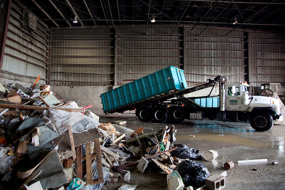 Truck empties large dumpster of solid commercial waste at transfer station