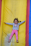 Talia Elgamil, 6, goes down an inflatable slide during the 2018 PTA Fall Festival at Lang Ranch Elementary in Thousand Oaks.