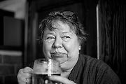 """Czech photographer Libuše Jarcovjáková drinking a beer at the """"Orlik"""" pub in Prague  where she spent long nights in the 1970's. Libuše Jarcovjáková's work is an authentic record of the life of a photographer who experienced everything she shot. She uses a personal, clearly-composed style, mixing the raw with the poetic. The street, night, sex, work, alcohol, love, and depression are captured with a self-destructive lack of restraint."""