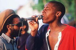 Man singing into microphone at outdoor concert,