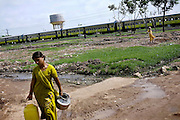 After having collected water, a lone woman is walking home in the impoverished New Arif Nagar colony, in Bhopal, Madhya Pradesh, India, near the abandoned Union Carbide (now DOW Chemical) industrial complex. Copyright: Alex Masi