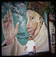 Pope John Paul mural  with brown paint splashed on the face, on Houston St, Manhattan.