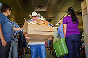07 AUGUST 2012 - TOLLESON, AZ: A client leaves after picking up meals at the food bank in Tolleson, AZ, about 15 miles west of Phoenix. The Tolleson food bank has been operating for more than 20 years. It used to serve mostly the families of migrant farm workers that worked the fields around Tolleson but in the early 2000's many of the farms were sold to real estate developers. Now the food bank serves both farm worker families and people who lost their homes in the real estate crash, that his Phoenix suburbs especially hard. More than 150 families a day are helped by the Tolleson food bank, an increase of more than 50% in the last five years.   PHOTO BY JACK KURTZ