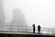 © Licensed to London News Pictures. 14/04/2015. Seaford, UK. Birdwatchers scan the mist for sea birds. . People in the early morning sea mist and sunshine in Seaford today 14th April 2015. Today is expected to be a very warm day across Britain. .. Photo credit : Stephen Simpson/LNP