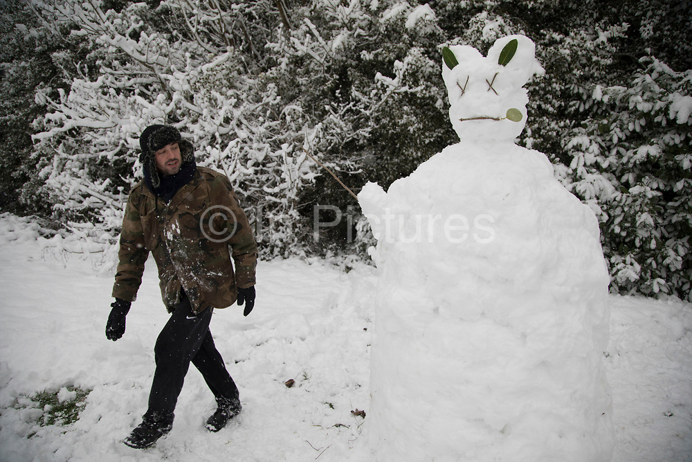 Man in Highbury Park in Moseley enjoying the heavy snow fall building a Donnie Darko inspired snow man on Sunday 10th December 2017 in Birmingham, United Kingdom. Deep snow arrived in much of the UK, closing roads and making driving treacherous, while many people simply enjoyed the weather.