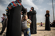 West Mosul residents wait for a bus for a refugee camp near Mosul, Iraq.<br />