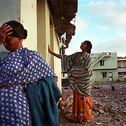 A woman cries while her daughter examines their former house in Nagappattinam, the site of vast tsunami destruction in the southeastern coast of India..The December 26, 2004 tsunami killed thousands of people along this coast, smashing boats, roads and houses and tearing thousands of families apart. .Picture taken February 2005 in Nagapptinam, Tamil Nadu, India, by Justin Jin