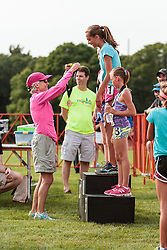 Youth mile, Joan Samuelson presents medals to podium winners