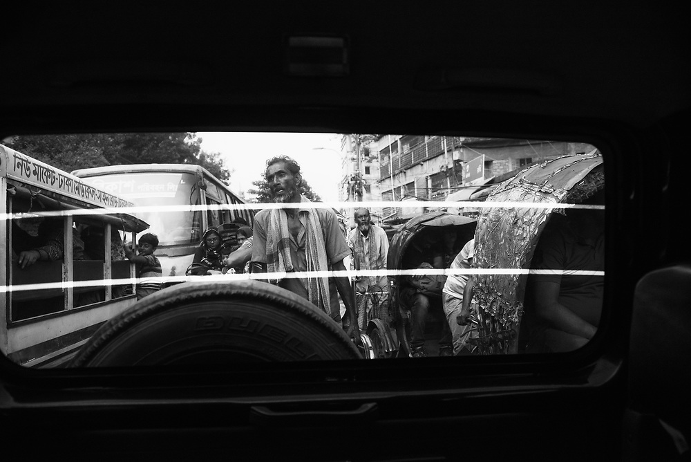 Dhaka, Bangladesh - November 1, 2017: A rickshaw driver works hard in heavy traffic in Dhaka. Photo taken through the back window of a motorized vehicle.