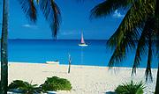Photographie en couleur de la plage d'Ouvéa prise depuis la cocoteraie. Il y a un voilier sur l'eau et une barque sur la plage