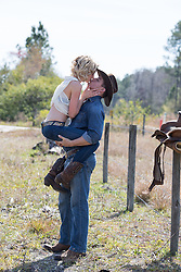 cowboy holding a girl up in his arms to get a kiss
