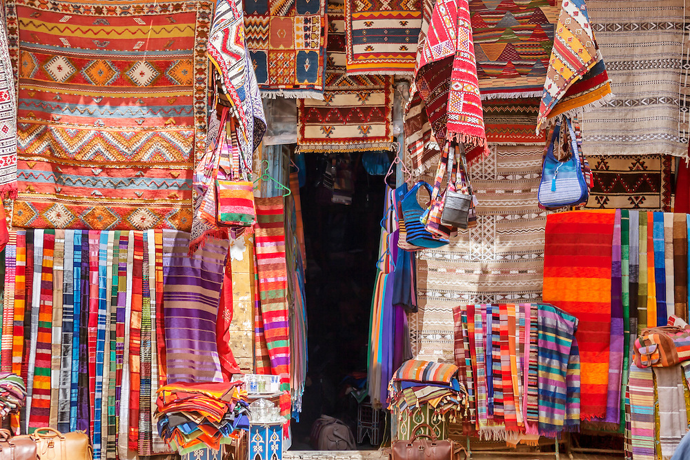 Carpet shop in Essaouira with colorful carpets hanging in front of the shop.