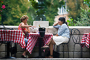 Two women sit at a table and talk outside a restaurant in Verona, Italy