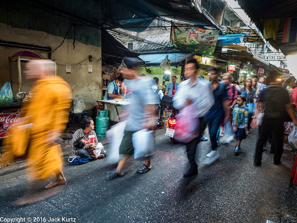 04 JANUARY 2016 - BANGKOK, THAILAND:        A monk and morning commuters walk past a beggar in the entrance to Bang Chak Market on the last day the market was open. The market closed January 4, 2016. The Bang Chak Market serves the community around Sois 91-97 on Sukhumvit Road in the Bangkok suburbs. About half of the market has been torn down. Bangkok city authorities put up notices in late November that the market would be closed by January 1, 2016 and redevelopment would start shortly after that. Market vendors said condominiums are being built on the land.      PHOTO BY JACK KURTZ
