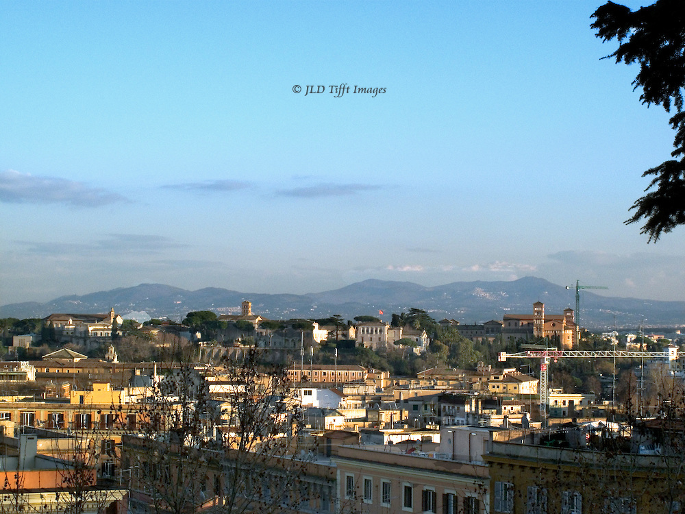 Rome, view from the Gianicolo (Janiculum)  hill at dusk.  Golden sunlight across the city roofs, hills beyond.