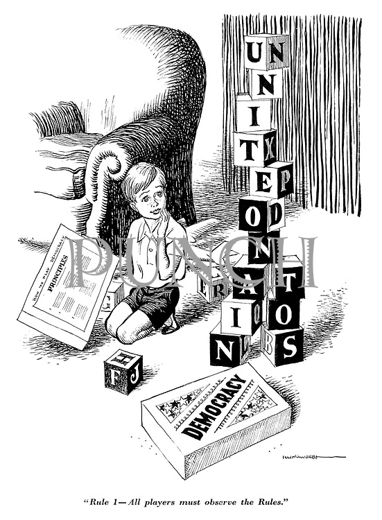 """Rule 1 - All players must observe the rules."" (Boy holds Principles of the game of Democracy while blocks of letters spell out United Nations)"