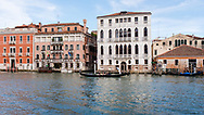 A gondola full of tourists glides along the canals of Venice, Italy