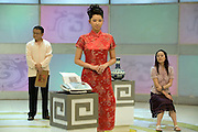 """An assistant waits for a fax to arrive from a panel of experts revealing if vases are real or fake on the set of """"Collector's World.""""  Participants bring their antiques to be appraised by experts and if the articles are deemed to be fakes they are smashed with a golden hammer."""