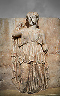 Roman Sebasteion relief sculpture of Ethnos with belted peplos, Aphrodisias Museum, Aphrodisias, Turkey.  Against a grey background.<br /> <br /> The matronly figure wears a belted classical dress (peplos) and held her long cloak up behind. The square hole above her shoulder with a corresponding hole in the back, was for lifting the finished relief into the ancient building by crane. .<br /> <br /> If you prefer to buy from our ALAMY STOCK LIBRARY page at https://www.alamy.com/portfolio/paul-williams-funkystock/greco-roman-sculptures.html . Type -    Aphrodisias     - into LOWER SEARCH WITHIN GALLERY box - Refine search by adding a subject, place, background colour, museum etc.<br /> <br /> Visit our ROMAN WORLD PHOTO COLLECTIONS for more photos to download or buy as wall art prints https://funkystock.photoshelter.com/gallery-collection/The-Romans-Art-Artefacts-Antiquities-Historic-Sites-Pictures-Images/C0000r2uLJJo9_s0