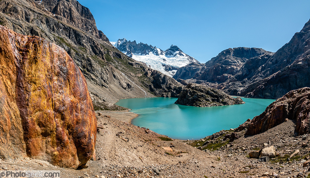"""The glacier-clad Marconi Range rises above Lago Electrico and oxidized red-orange rocks near the unmarked turn to Lago Pollone trail. El Chalten, Santa Cruz Province, Argentina, Patagonia, South America. We hiked the scenic Rio Electrico Valley to Refugio Piedra del Fraile (""""Stone of the Friar"""", 14.5 km round trip). From the refuge, a rewarding day hike visits Lago Pollone (8.5 km round trip with 320 m gain). This image was stitched from multiple overlapping photos."""