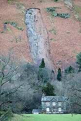 © Licensed to London News Pictures. 10/12/2015. Patterdale UK. Picture shows a huge landslide behind a house in Patterdale near the village of Glenridding that has flooded for a second time this week after the beck broke it's banks. Photo credit: Andrew McCaren/LNP