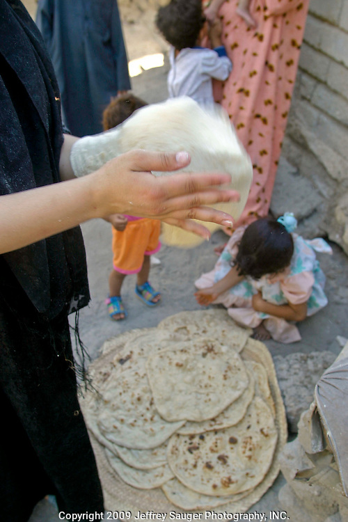 A woman makes traditional Iraqi flat bread during the Al-Kasid family's Istikbal, or homecoming, in their home village Suq ash Shuyukh, about 20 miles southeast of Nasiriyah, Iraq, Wednesday, July 30, 2003...The women spend most of their time making dough, baking bread, milking cows, taking care of children, preparing food, etc. as the men gather out front of the compound. The women wear black as a sign of mourning for a close loved one that has died; some for a year and some forever after the death.