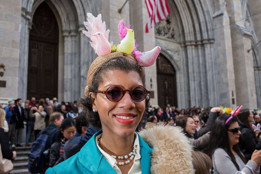New York, NY, USA-27 March 2016. A woman with an elegant hat topped by three pastel birds in front of St. Patrick's Cathedal in the annual Easter Bonnet Parade and Festival.