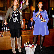 NLD/Amsterdam/20100328 - Veiling voor Engelen van Oranje, Fanny Koopmans, partner van Boy Waterman en Magali Gorree tonen veilingitem flessen organic champagne inclusief sabel