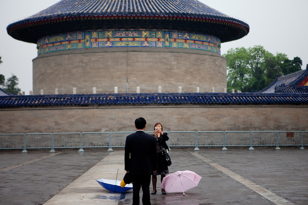 """Woman taking a photograph of her husband at """"The Temple of Heaven"""" which is a complex of Taoist buildings situated in the southeastern part of central Beijing. Beijing is the capital of the People's Republic of China and one of the most populous cities in the world with a population of 19,612,368 as of 2010."""