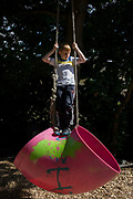 Boy swings on rope in risk averse playground called The Land on Plas Madoc Estate, Ruabon, Wrexham, Wales. Young people are encouraged to push their personal limits in a way that parents are nowadays scared to allow. But here in this council play park, children are encouraged to experiment with risk aversion, to enjoy a wilder form of play and interaction with others - the opposite of online relations and over safe childhoods. From the chapter entitled 'Playing with Fire' from the book 'Risk Wise: Nine Everyday Adventures' by Polly Morland (Allianz, The School of Life, Profile Books, 2015).