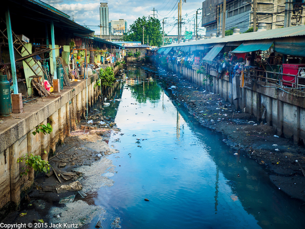 """12 JUNE 2015 - BANGKOK, THAILAND: A waste water canal running through Khlong Toey Market in Bangkok. Khlong Toey Market in Bangkok. Khlong Toey (also called Khlong Toei) Market is one of the largest """"wet markets"""" in Thailand. The market is located in the midst of one of Bangkok's largest slum areas and close to the city's original deep water port. Thousands of people live in the neighboring slum area. Thousands more shop in the sprawling market for fresh fruits and vegetables as well meat, fish and poultry.          PHOTO BY JACK KURTZ"""