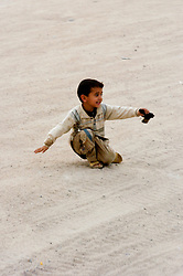 A young Iraqi child waving what is probably a real handgun  runs, jumps and falls as he tries to keep up with  British Army patrol of Royal Dragoon Guards passes through Umm Qasr area Southern Iraq, while on Op-Telic in March 2005